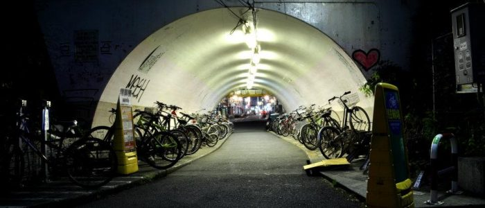 A lit up tunnel filled with bicycles.